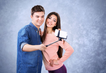 Teenager couple making photo by their self with mobile phone on grey background