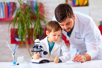 teacher helps kid to conduct experiment with microscope