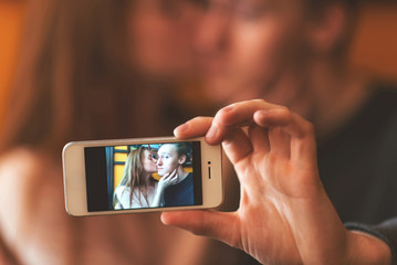young couple kissing and photographing themselves on the phone