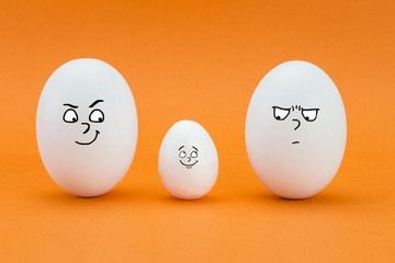 two big eggs look with face of few friends at a small egg