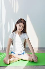 little girl doing gymnastics on a green yoga mat. doing fitness exercise, on white background. children's fitness, yoga for kids
