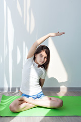 little girl doing gymnastics on a green yoga mat. children's fitness, yoga for kids. doing fitness exercise, on white background.