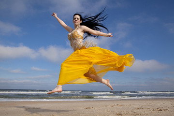 Pretty belly dancer dancing on a beach with ocean in the background
