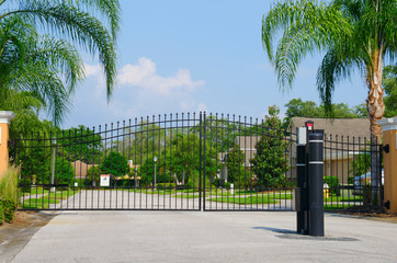 Entrance gate to a beautiful gated residential house community with lush green trees and grass