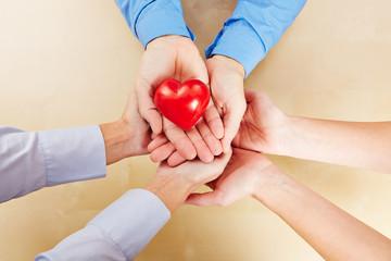 Viele Hände halten ein rotes Herz