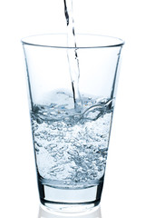 pouring bubbling water into half full glass