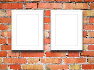 Close-up of two blank white picture frames on orange brick wall background
