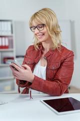 geschäftsfrau im büro mit handy und tablet
