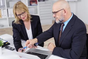 geschäftsmann zeigt einer kollegin etwas am laptop