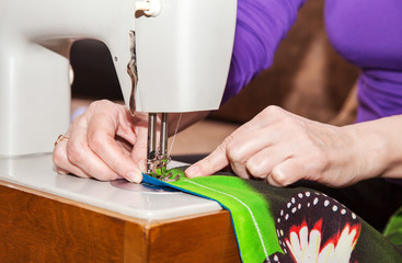 woman's hands sewing on the sewing machine