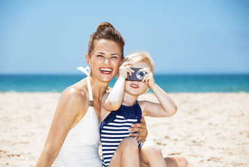 Smiling mother and child taking photos with camera at beach