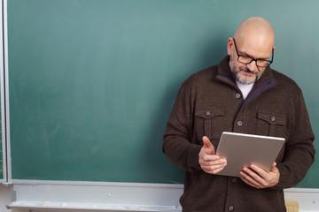 älterer lehrer mit tablet vor der tafel
