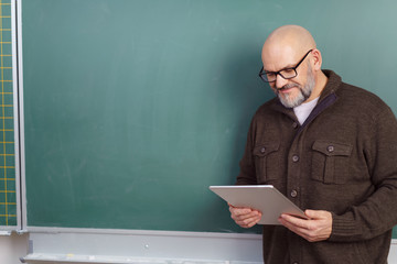 lehrer steht mit einem tablet vor der tafel