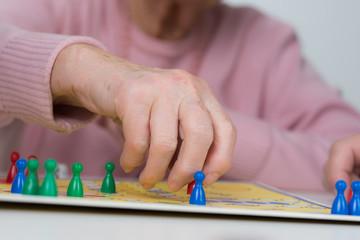 seniorin spielt mit unterstützung ein brettspiel