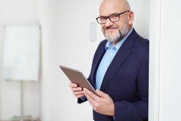 manager lehnt an der tür zum büro und hält sein tablet in den händen