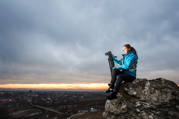 Portrait of cute female photographer sitting on the big rock at city overview point at the sunset with her camera on tripod. Woman is enjoying of the beautiful view
