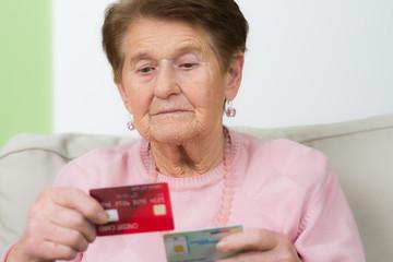 betagte frau schaut sich versicherungskarten an
