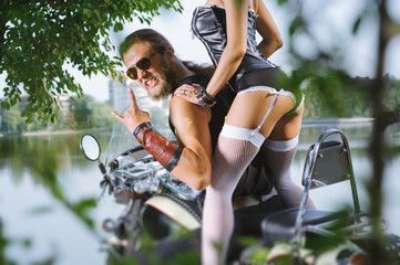 Portrait of long-haired biker guy and girl in sexy lingerie on the motorcycle. Rear view. Man wearing sunglasses and giving the devil horns gesture. Woman bottom, close up. Tilt lens blur effect