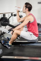 Muscular man on rowing machine drinking water