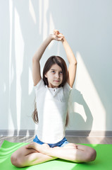 lotus Pose. little girl doing gymnastics on a green mat for yoga. doing fitness exercise and stretching in a bright room. children's fitness, yoga for children.