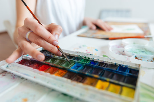 Set of watercolor paints used by woman artist on table
