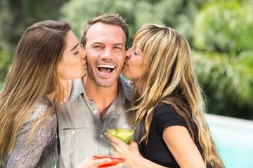 Beautiful women kissing happy man