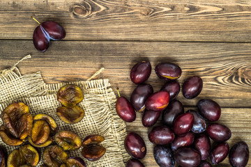 Fresh prune plums on wood background.