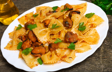 pasta with mussels and parsley on a wooden background