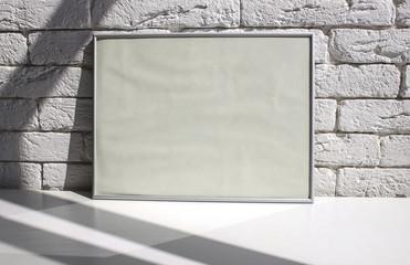 Aluminum frame on a white table against a white brick wall. Template.