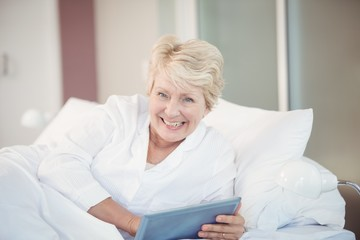 Portrait of happy senior woman using digital tablet