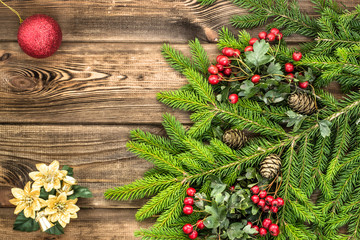 Christmas tree branch of spruce with christmas decoration on wooden table