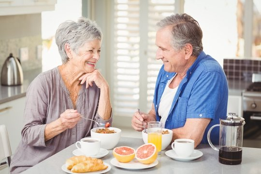 Happy senior couple discussing while having breakfast