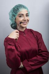 Dentista con cuffietta verde e camice  ci mostra uno specchietto professionale guardando in macchina