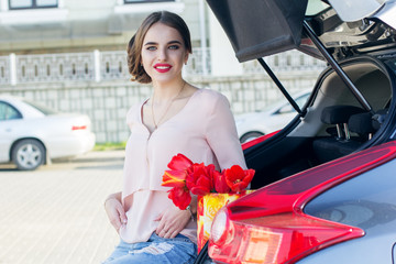 Girl with red tulips sitting in car trunk