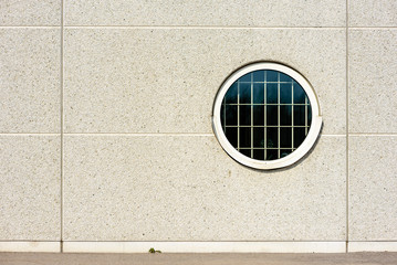 Circular window with metal bars on the inside, Copy space on facade outside.