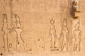 The south wall of the temple of Hathor at Dendera with lion-headed waterspouts. Cleopatra and her son Caesarian (on the left side)