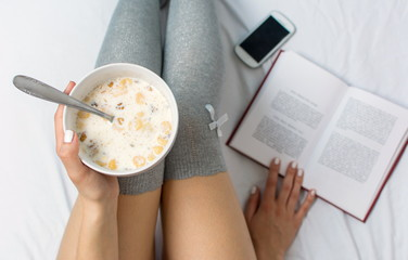 Woman eating cereals and reading in bed