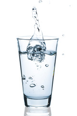 Water glass with splashing water and waterdrops