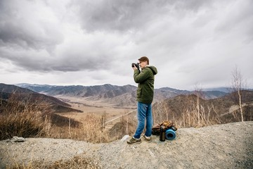 man with a camera stay on the background of mountains