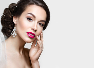 Beautiful brunette girl with perfect skin, evening make-up, wedding hairstyle and accessories.Beauty face.