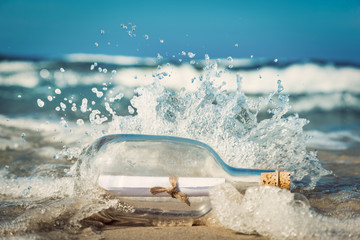 Message in the bottle coming with wave from ocean