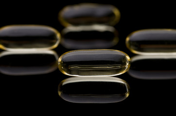 Cod liver vitamin D capsules on black reflective surface