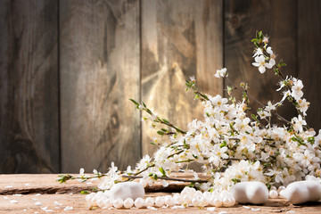 Spring flowers, heart and perls on wooden background
