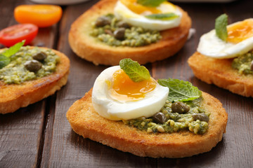 Fresh toasts with pesto and egg on wooden background