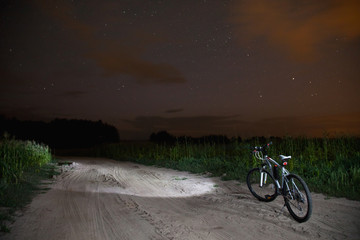 starry sky, night photography, astrophotography, tree silhouettes, big bear, white mountain bike with a flashlight standing on the field