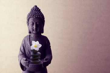 Buddha statue on a beige background with flower