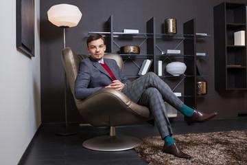 Стильный молодой мужчина сидит в кресле скрестив ногу на ногу