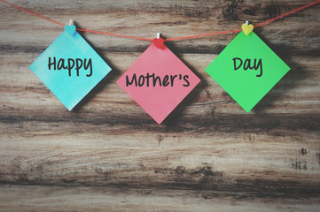 Happy mother's day on colorful paper with clothespin hanging on a string with wooden background, retro style.