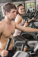 Happy man and woman exercising on the elliptical machine