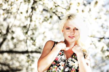 Hübsche blonde Frau vor Kirschblüten im frühling